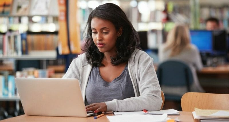 Student studying on laptop in the library