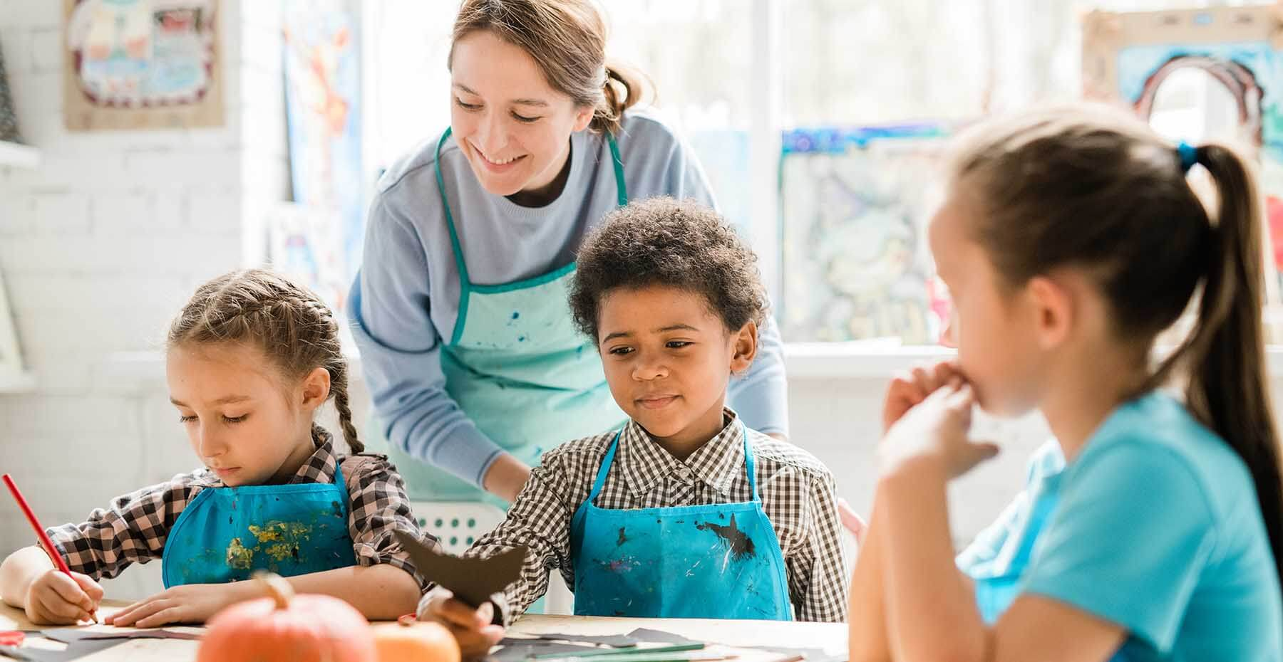 Children in aprons painting with teacher