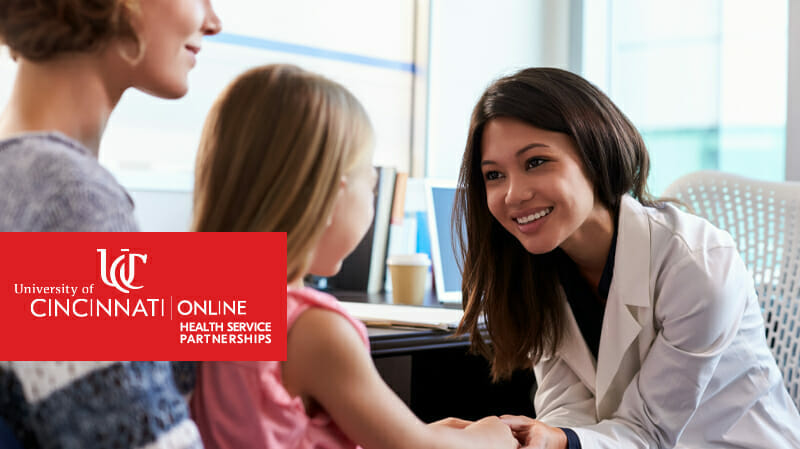 Smiling health professional holding hands of little girl