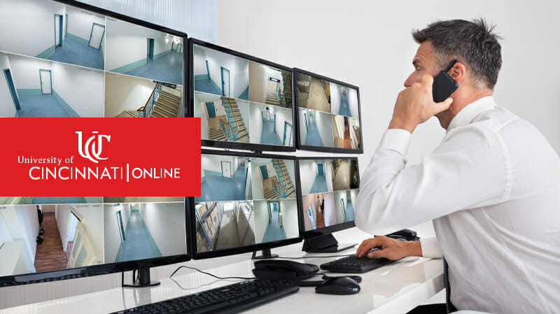 Man looking at computer monitors while on phone