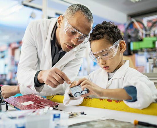 Man teaching child in labcoats