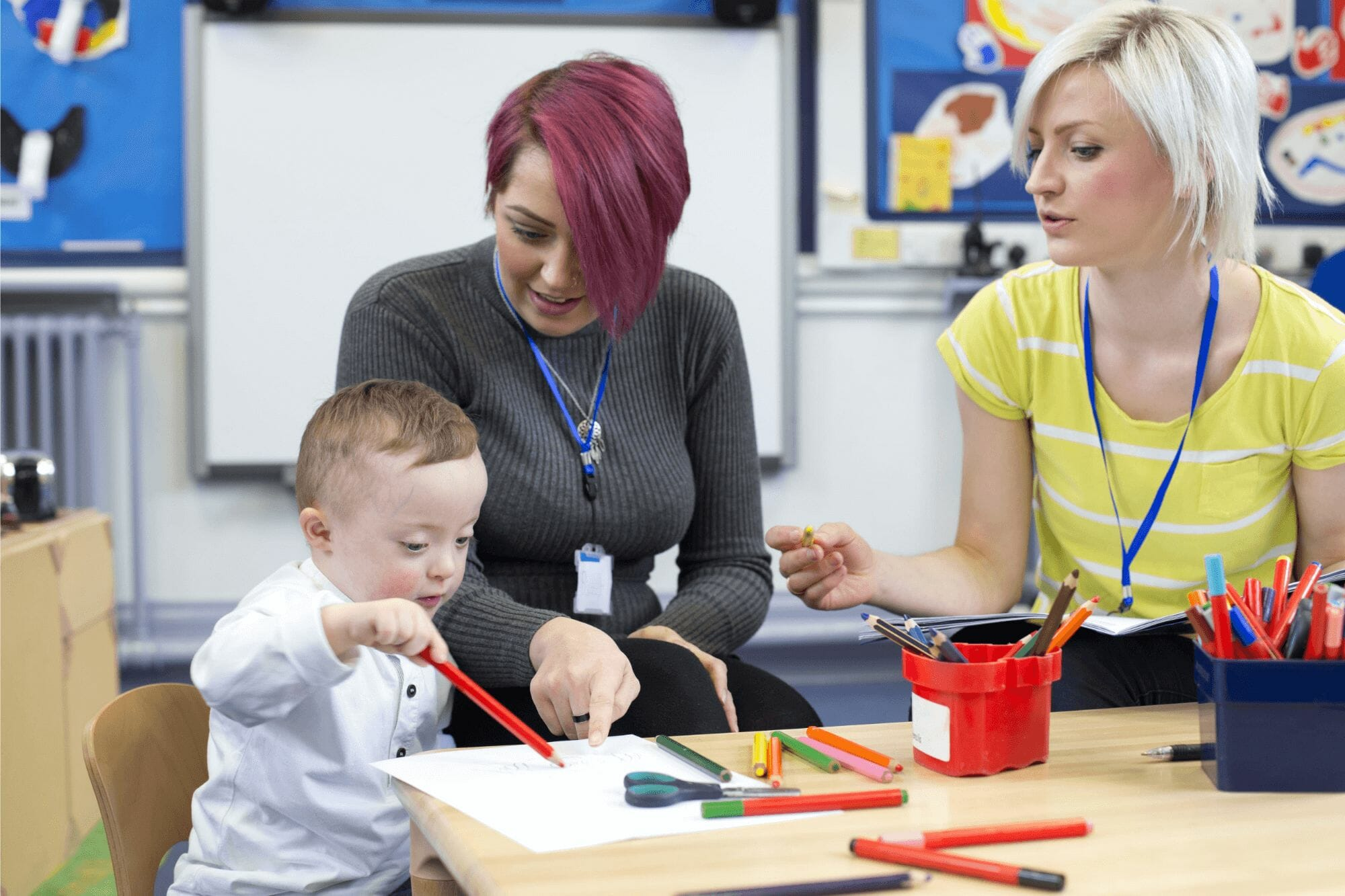 Two female teachers coloring with child